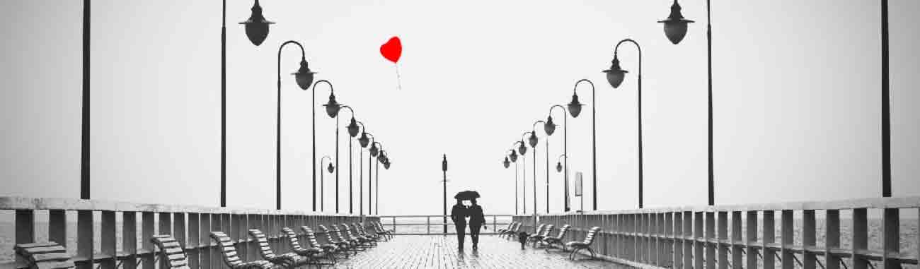 Mann und Frau auf einer Seebrücke bei Regen